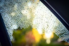 Outside broken window car smashed by thief for insurance concept. Outside close-up view broken passenger window car smashed by thief or accident. Damaged glass stock photos