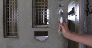 Hand opening cell door with sound. Outside cell in prison with hand opening or unlocking door with sound stock video footage