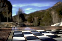 Outside chessboard amongst the trees. Chessboard found in a park along the riverwalk awaiting the games ahead Stock Photo