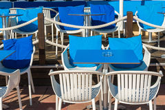Outside dining area. White chairs and blue tables at the outside dining area on sunny day Stock Image