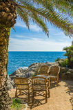 Outside dining table. Wicker chairs and table under the palm tree with a wonderful sea view Royalty Free Stock Photo