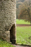 Outside doorway to ancient castle turret. Picture of a turret with open doorway leading to footpath. Ancient building set in green countryside royalty free stock images
