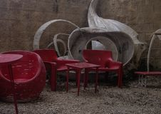 Outside empty cafe red chairs and table with white modern design, on little stones covered veranda royalty free stock image