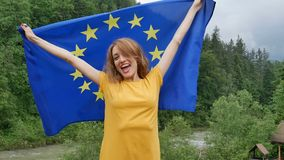 Outside female portrait of young patriotic girl in yellow casual dress holding flag of the European Union over green. Forest background during spring day, HD stock video
