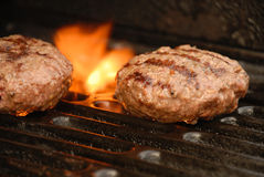 Outside grilling season. Close up of hamburgers grilling on the grill Royalty Free Stock Photo