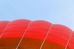 Outside of a hot air balloon. Image of the Outside of a red hot air balloon against a blue sky royalty free stock photo