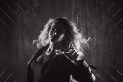 Outside of the law. Attractive femme blonde behind the fence mesh. Black and white toning. Rock`n`roll girl, young beautiful girl dances in a dark alley, against Royalty Free Stock Images