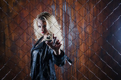 Outside of the law. Attractive femme blonde behind the fence mesh. Rock`n`roll girl, young beautiful girl dances in a dark alley, against the fence mesh Royalty Free Stock Image