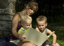 Outside learning. Family reading a book while on an outside trip stock photos