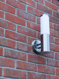 An outside metal and white modern lamp turned off not on near fr. Ont door in the day light and on brick wall behind domestic cool silver Royalty Free Stock Images
