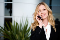 Outside of the office. Attractive blond business woman talking on cell phone while standing outside of an office building Stock Image