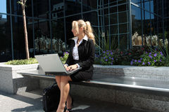 Outside office. Pretty businesswomen working on a laptop outside stock photo