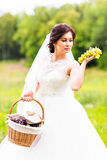 Outside portrait of beautiful young bride with grapes in a park Stock Photography