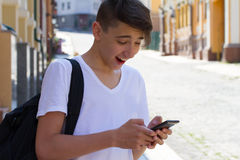 Outside portrait of teen boy. Handsome teenager carrying backpack on one shoulder and smiling, communicating by phone. Stock Photo
