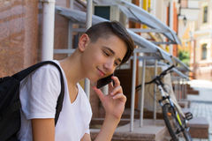 Outside portrait of teen boy. Handsome teenager carrying backpack on one shoulder and smiling, speaking by phone. Royalty Free Stock Photo