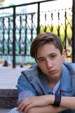 Outside portrait of teen boy. Handsome teenager  sitting on the stairs alone. Royalty Free Stock Images