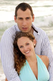 Outside portrait of young attractive happy couple. Young couple at the beach in the gulf of mexico having a discussion with waves crashing behind them Royalty Free Stock Images