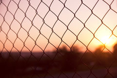 Outside rusty wire fence with sunset Stock Photography