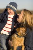 Outside Together. A mother her young son and the family dog together laughing on a park bench Stock Image