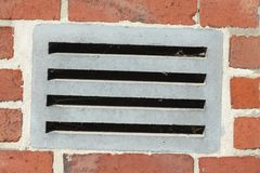 Outside ventilation slits. On a red brick wall Stock Image