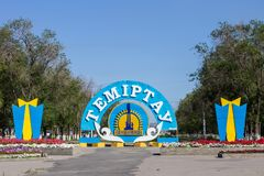 Outside view of the Main Avenue with colorful Emblem and Flag of City Temirtau on the End of the main Promenade. Entrance from royalty free stock images