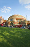 Outside view of Royal Albert Hall on sunny day. London, UK - May 26, 2013 : Outside view of Royal Albert Hall with green grass field, people and cars present on Stock Photography