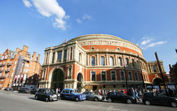 Outside view of Royal Albert Hall on sunny day. London, UK - May 26, 2013 : Outside view of Royal Albert Hall, people and cars, particularly london taxi cabs Stock Photography