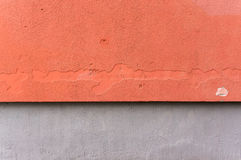 Outside wall with aged orange colored ornate plaster and gray Royalty Free Stock Photo