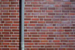 Outside wall, bricks and down pipe, background pattern Royalty Free Stock Photos