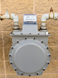 Outside wall natural gas meter supply plumbing. Residential natural gas meter on exterior wall to measure household energy consumption Royalty Free Stock Photography