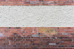 Outside wall with plastered area between red clinker brick, text Stock Image