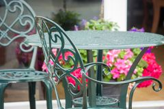 Outside wrought iron table and chairs. An outside green iron table and chairs, with pink and purple flowers in the background stock photos