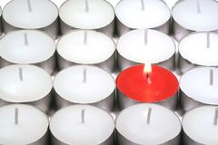 Outsider. One red candle amongst white ones stock photography