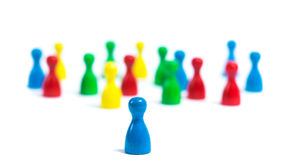 Outsider. Single board game figure standing in the front, big group of individuals in the back. Symbol of leadership Royalty Free Stock Photo