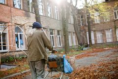 Outskirts of the city, homeless man walking and pushing cart. Stock Photo