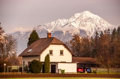 Outskirts of Zagreb: Traditional Rural House with Snow Capped Mountain Background royalty free stock photos