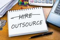 Outsource. Memo in notebook with part of laptop, receipts and calculator Royalty Free Stock Photo