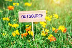 Outsource signboard. Outsource on small wooden signboard in the green grass with flowers and sun ray royalty free stock photography