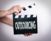 Outsourcing. Female hands holding movie clapper Stock Images
