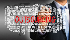 Outsourcing with related word cloud handwritten by businessman Royalty Free Stock Photo
