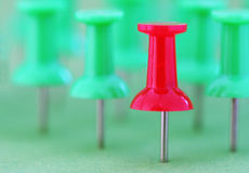 Outstanding. Team of pushpins with one standing out from the crowd. Shallow DOF to additionally isolate the sharp, red pushpin royalty free stock photo