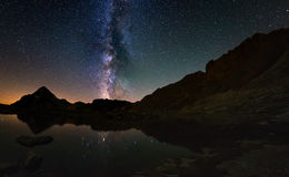 The outstanding beauty of the Milky Way arc and the starry sky reflected on lake at high altitude on the Alps. Fisheye scenic dist. Ortion and 180 degree view Royalty Free Stock Photo