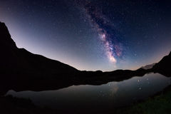 The outstanding beauty of the Milky Way arc and the starry sky reflected on lake at high altitude on the Italian Alps, Torino Prov. Ince. Fisheye scenic Royalty Free Stock Photography