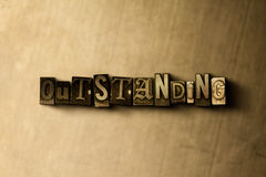OUTSTANDING - close-up of grungy vintage typeset word on metal backdrop Stock Images