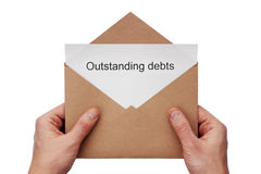 Outstanding debts. A hand hold a craft envelope with message about outstanding debts, isolated white at the studio Stock Image
