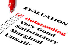Outstanding Evaluation. Red pen on evaluation, with outstanding checked Royalty Free Illustration