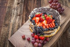 Festive fruit cake. Outstanding fruit cake with strawberries, blueberries, grapes and chocolate. Celebratory tart stock image