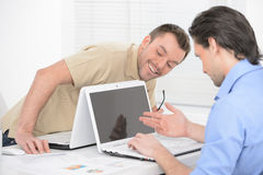 Outstanding news. Two cheerful business people looking at the co Stock Photography