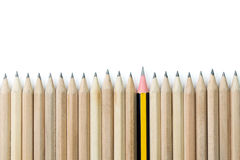 Outstanding. One pencil standing out from the row of brown pencils Stock Photo