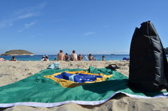 Outstretched Flag of Brazil and a Black Backpack on the sand of Barceloneta Beach in Barcelona, Spain Royalty Free Stock Photography